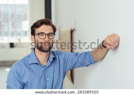 Thoughtful bearded businessman wearing glasses leaning on the wall staring ahead with a pensive expression - stock photo