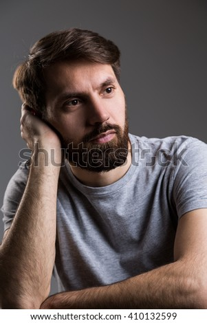 Thoughtful bearded man with head leaning on hand on dark grey background