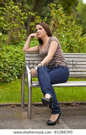 thoughtful beautiful brunette woman sitting on a bench in a park and looking at something