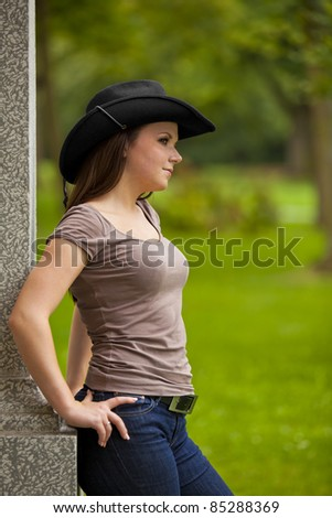 thoughtful beautiful brunette woman with a cowboy hat standing outside a building in a park and looking at something - stock photo