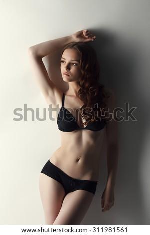Thoughtful beautiful model posing in lingerie - stock photo