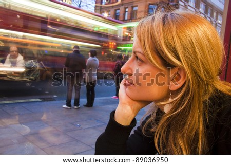 Thoughtful beautiful young lady looking at the street through the cafeteria window.. Blurs of London's traditional bus driving by and some reflexions from the interior can be seen in the glass - stock photo