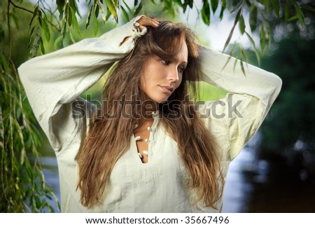 Thoughtful beautiful young woman in the willow leaves - stock photo