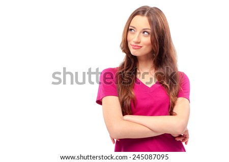 Thoughtful beauty. Beautiful young woman looking away and keeping arms crossed while standing isolated on white - stock photo