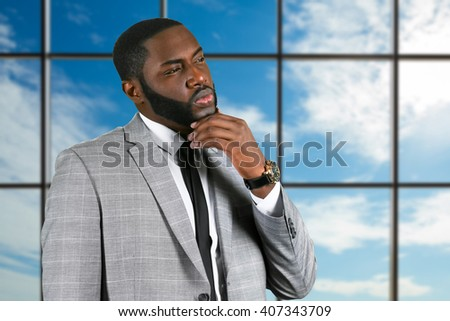 Thoughtful black businessman in suit. Pensive manager on sky background. In search of bright idea. He needs inspiration. - stock photo