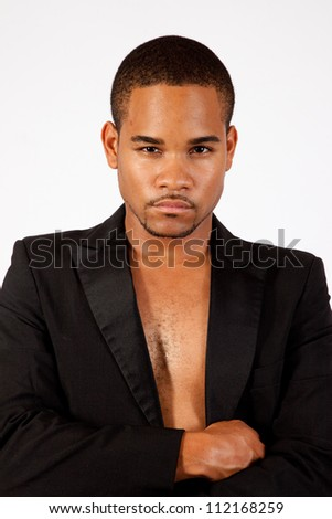 Thoughtful black man without a shirt on, but in a black tux jacket, with his arms crossed