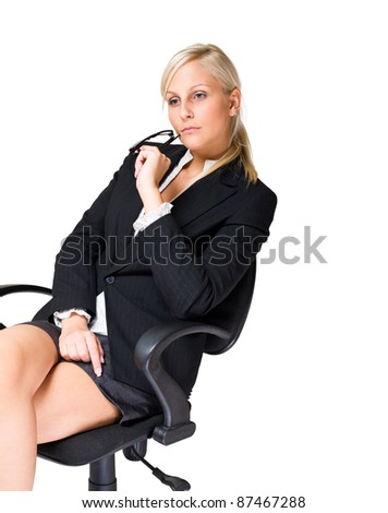 Thoughtful blond business woman sitting in office chair. - stock photo