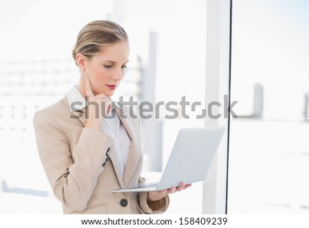 Thoughtful blonde businesswoman using laptop in bright office