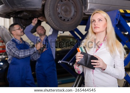 Thoughtful blonde girl with credit cards at auto repair shop