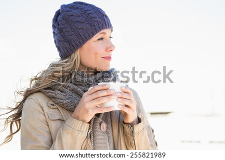 Thoughtful blonde in warm clothes holding hot beverage in the city - stock photo