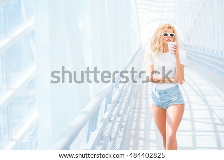 Thoughtful blonde young woman in sunglasses with take away coffee cup posing on the urban bridge.
