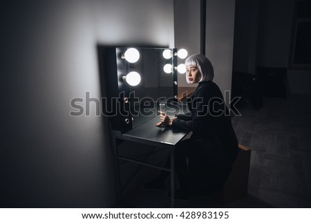 Thoughtful blonde young woman sitting and drinking champagne near the mirror in dressing room  - stock photo