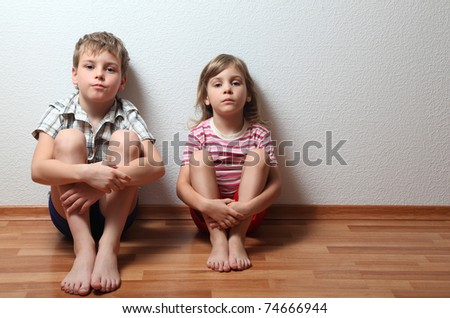 Thoughtful boy and girl in home clothes sit leaning on the wall - stock photo