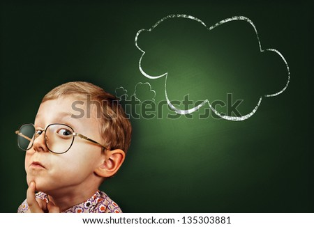 Thoughtful boy funny portrait with abstract idea clouds on chalkboard - stock photo