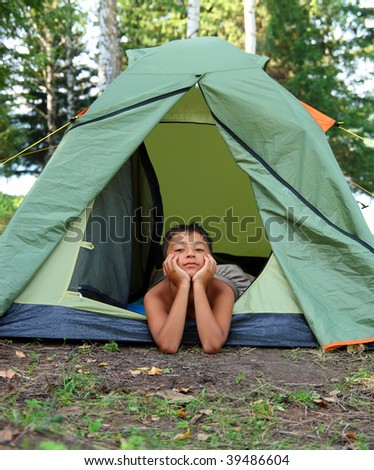 thoughtful boy in camping tent summer forest - stock photo