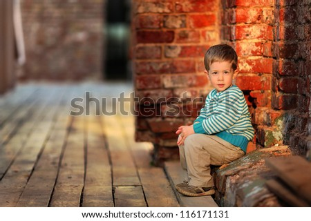 thoughtful boy sits near a stone wall