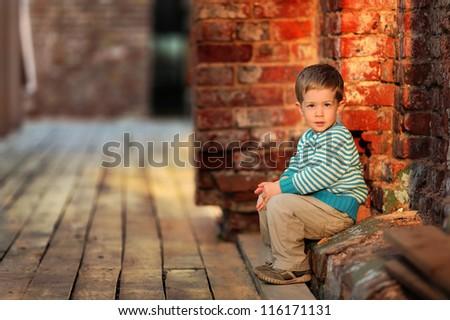 thoughtful boy sits near a stone wall - stock photo