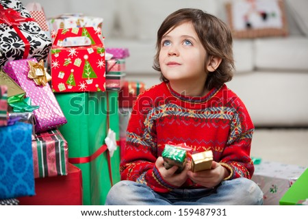 Thoughtful boy sitting by stacked Christmas gifts at home - stock photo