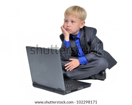 Thoughtful boy with computer, isolated on white background - stock photo