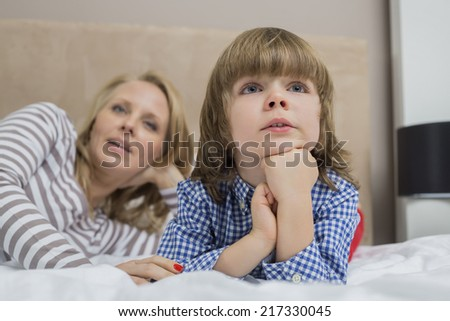 Thoughtful boy with mother in bed - stock photo