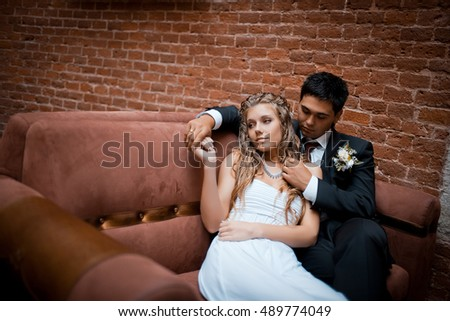 Thoughtful bride lies on groom's shoulder while he sits on soft red couch