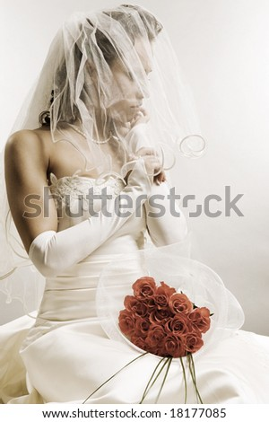 thoughtful bride sitting with bunch of roses - stock photo