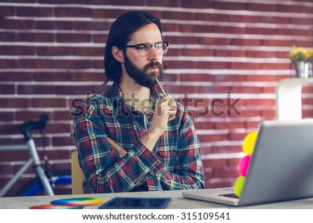 Thoughtful businesman with laptop working in creative office - stock photo