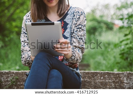 Thoughtful business girl looking to the digital tablet screen while sitting in nature. Business woman browsing internet or connecting to wireless via touchscreen pad. copy space - stock photo