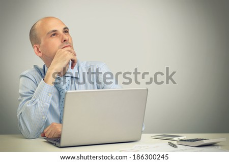 Thoughtful business man working on a laptop - stock photo