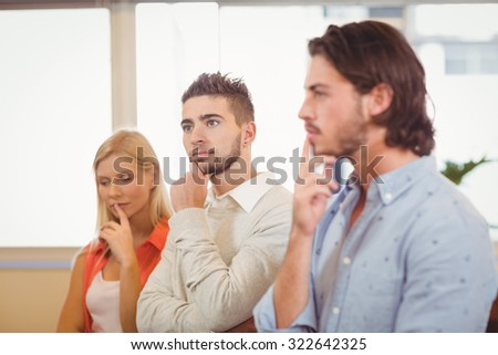Thoughtful business people with hand on chin looking away in creative office