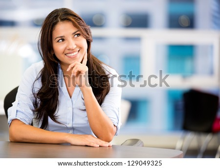 Thoughtful business woman at the office looking up - stock photo