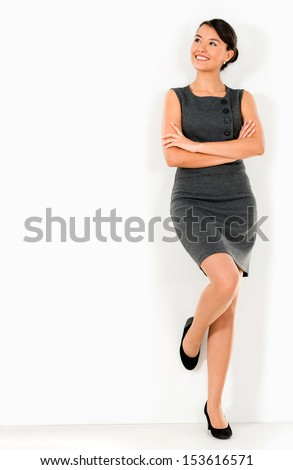 Thoughtful business woman leaning against the wall  - stock photo