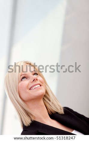 Thoughtful business woman looking up and smiling - stock photo