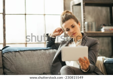 Thoughtful business woman using tablet pc in loft apartment - stock photo