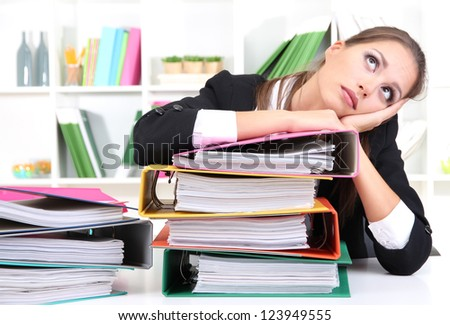 thoughtful business woman with documents in her workplace - stock photo