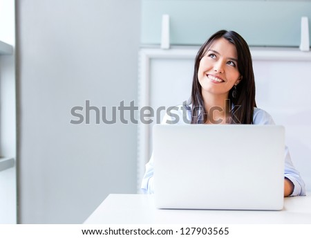 Thoughtful business woman working on a laptop - stock photo