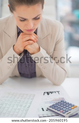 Thoughtful business woman working with documents - stock photo