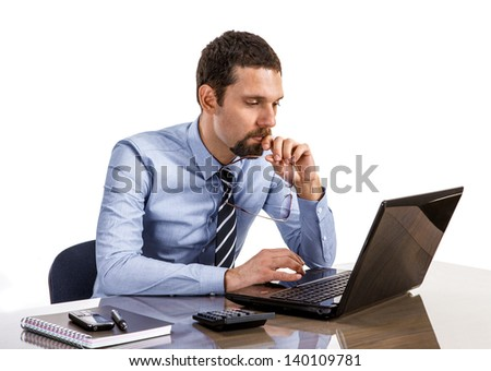 thoughtful businessman at office desk looking on laptop isolated on white background  - stock photo