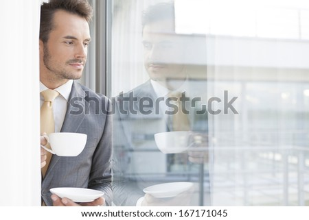 Thoughtful businessman having coffee in office - stock photo