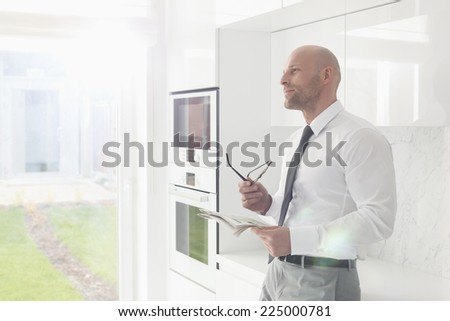 Thoughtful businessman holding newspaper at home - stock photo