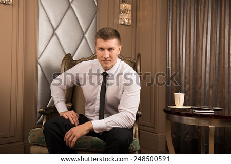 Thoughtful businessman in chic interior. thoughtful young man in a business suit sitting on the armchair with his legs crossed and keeps his hand on his chin  - stock photo