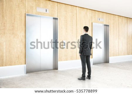 Thoughtful businessman in interior with two silver elevators, wooden wall, concrete floor and ceiling. Choice concept. 3D Rendering