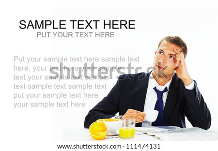 Thoughtful  businessman looking up with concentration and having breakfast - stock photo