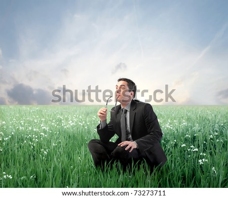 Thoughtful businessman on a green meadow - stock photo