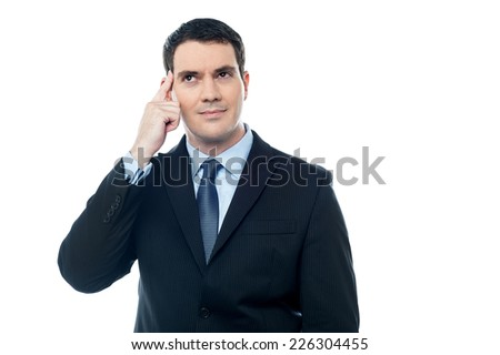 Thoughtful businessman pointing at his head with his finger - stock photo