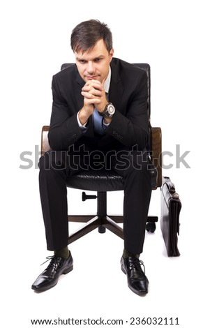 Thoughtful businessman sitting in an armchair  isolated over white background - stock photo