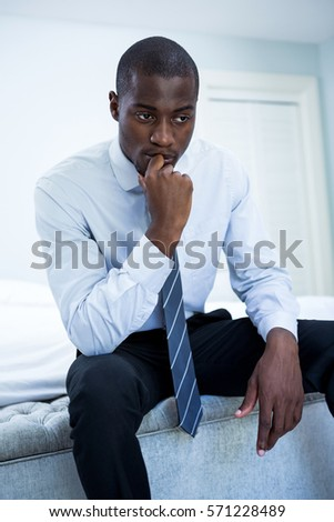 Thoughtful businessman sitting on bed in bedroom