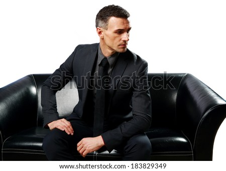 Thoughtful businessman sitting on the sofa isolated on a white background