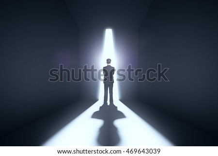 Thoughtful businessman standing against abstract bright light in concrete room. Research concept
