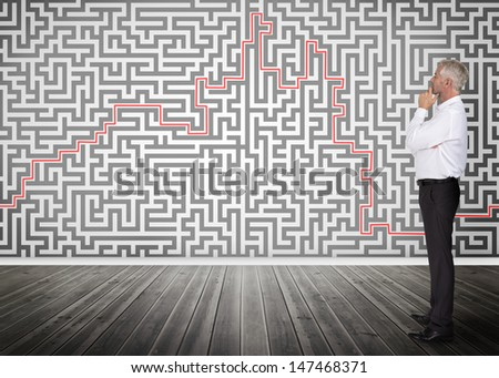 Thoughtful businessman standing and looking at a maze on a wall - stock photo